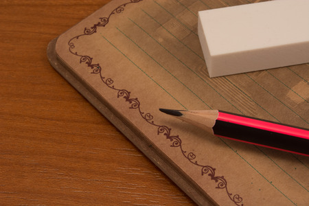 pencil eraser: Pencil eraser and notebook on wooden table Stock Photo