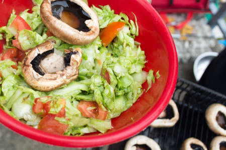 Ball filled up with fresh salad and grilled mushrooms. Barbecue visible in the background