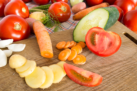 Sliced vegetables on a wooden plate in the kitchen Stock Photo