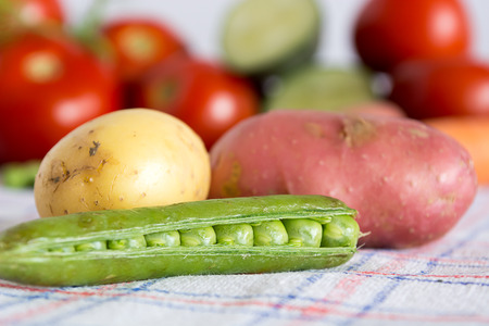 Green beans with potato on a kitchen table with blurred background with other vegetables Stock Photo