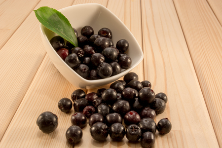 sorb: White bowl full with fresh and tasty aronia spilled on wooden table Stock Photo