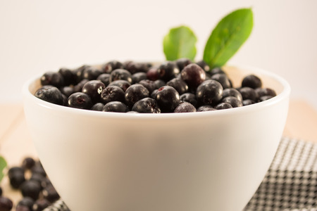 White bowl full with fresh and tasty aronia