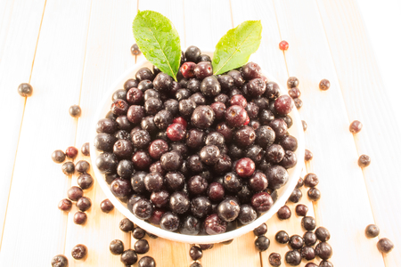 sorb: Fresh and tasty aronia spilled out of a bowl. Water droplets on fruit are visible