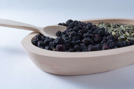 Aronia and pumpkin seeds in wooden bowl with wooden spoon isolated on white background