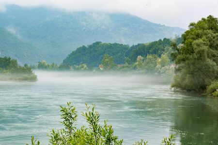 RIver Drina with haze in early morning. Cloudy mountain in background Stock Photo