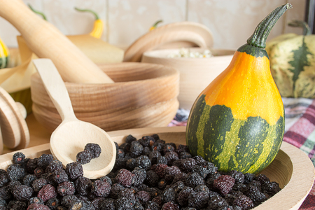 sorb: Chokeberry in small wooden plate with decorative pumpkin in it