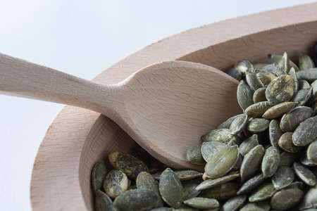 sorb: Pumpkin seeds in wooden bowl with wooden spoon isolated on white background