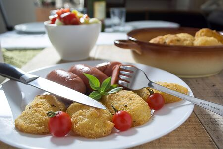mouthwatering: Pork sausages and breaded potatoes fried in a dish and decorated with cherry tomato. Fork and knife next to dish