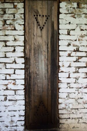 preservatives: Rustic smokehouse door on white brick wall