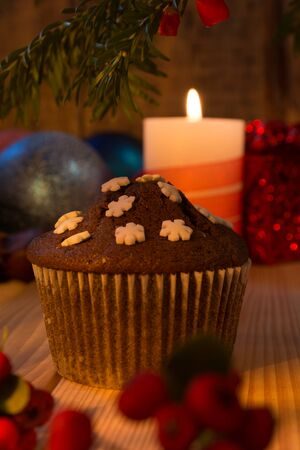 Decorated table with cup cakes on Christmas Eve lit by candles Stock Photo