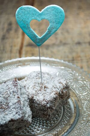 Close up of chocolate cakes with coconut flour on the glass plate with blue ornaments