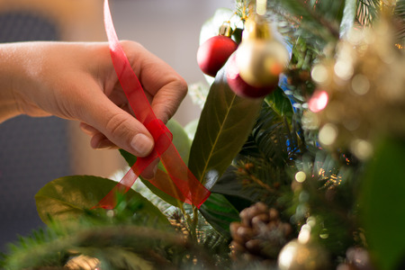 Girl decorating Christmass bouqet  with red ornaments, pines and tree branches