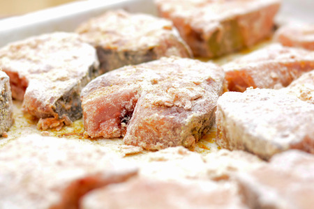 Fish steaks covered with wheat flour and bread crumbs on the baking plate