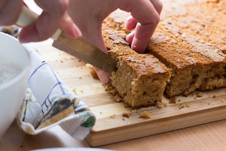 pound cake: Female hands cutting and preparing cake crust on wooden  plate