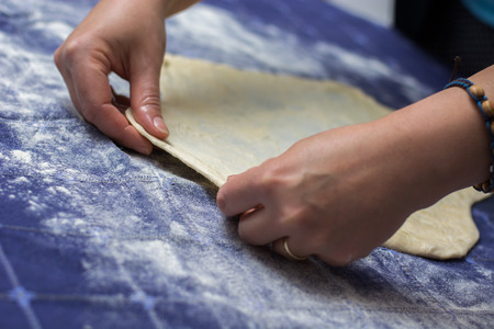 Creating homemade Phyllo or strudel dough on a home table cloth for cheese pie or other kind of traditional pastry.