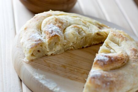 Fresh and delicious cheese pie cut on the wooden plate ready to be served to the guests