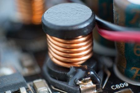 transistor: Un polvoriento equipo de componentes. Detalle de una placa base de computadora polvorienta. Condensador electrolítico y conductor visible en la placa de circuito impreso. Enfoque selectivo
