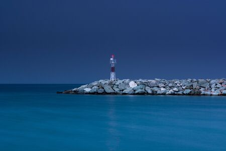 Small red lighthouse in Platamonas Greece. Long exposure shot by night.