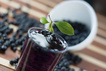 Bowl full of aronia spilled on wooden table with glass of aronia juice