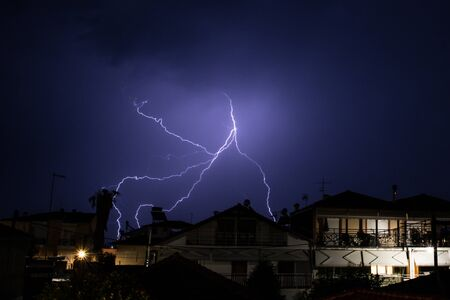 Lightning display over houses in Greece in the summertime Stock Photo