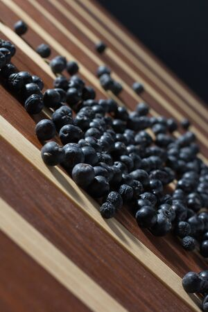 Fresh and tasty aronia spilled on wooden table Stock Photo