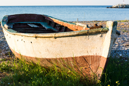 Old boat on the seashore covered with grass with calm sea in the background Stock Photo