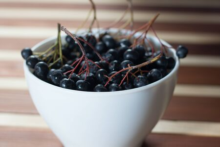 Closeup of wet aronia berries in white simple bowl on wooden table