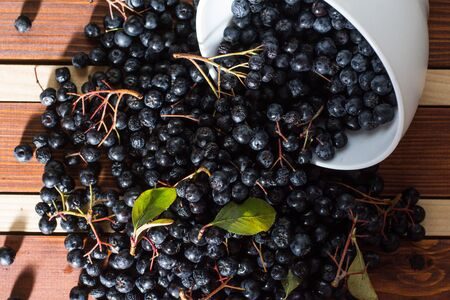 White bowl full with fresh and tasty aronia spilled on wooden table Stock Photo