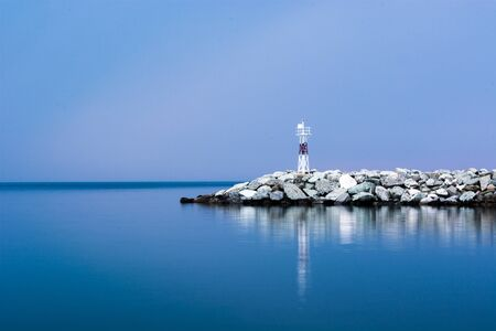 Small red lighthouse in Platamonas Greece. Long exposure shot by day