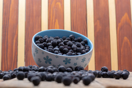 Spilled white bowl full with frozen aronia berries on wooden rustic table