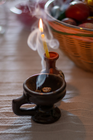A burning candle on the table in the home of ortodox people at easter.