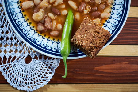 Beans with smoked pork on dinner plate with spelta bread and pepper on the plate