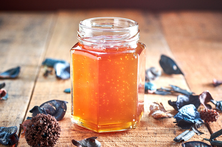 Glass jar full with honey on wooden table. High contrast
