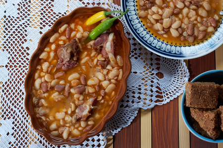 Beans with smoked pork on dinner plate with spelta bread Stock Photo