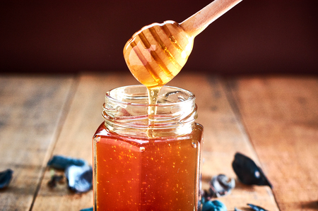 Glass jar full with honey. Taking honey with wooden spoon