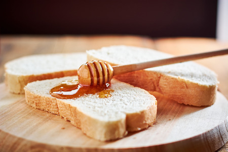 Pouring fresh honey on bread slices with wooden spoon Stock Photo