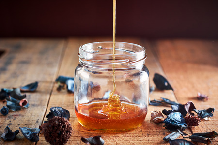 Pouring golden honey in the glass jar on wooden table Stock Photo