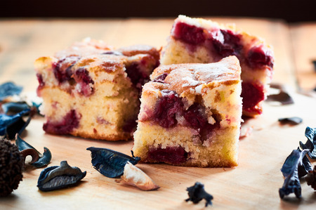 Cake with cherries on wooden table with shugar on top