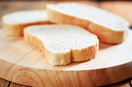Fresh slices of bread on wooden plate. with shallow depth of field