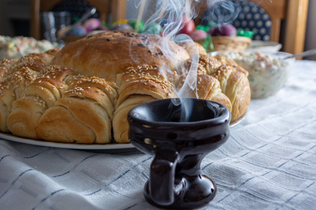 Smoke rising from Cresset on the table with food on ortodox easter Stock Photo