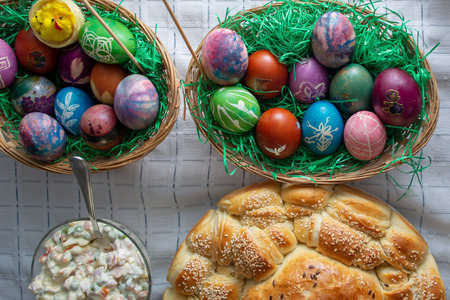 Table ful of food on easter holyday. Colored eggs and bread shoot from upper angle Stock Photo