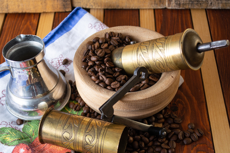 Coffee ready to be milled with old grinder. Coffee is in the table Stock Photo
