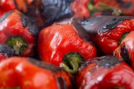 Red peppers roasting on a wood-fired stove in preparation for making ajvar, a traditional serbian dish Stock Photo