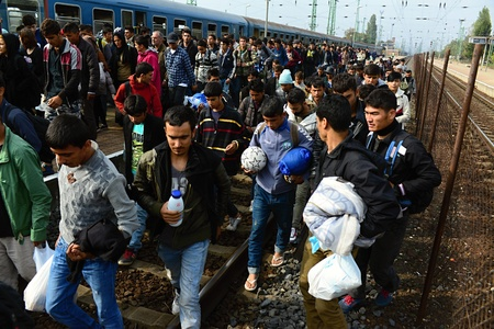 and germany: October 6,2015; Hegyeshalom in Hungary. Group of refugees leaving Hungary. They came to Hegyeshalom by train and then they leaving Hungary and go to Austria and then to Germany. Many of them escapes from home because of civil war.