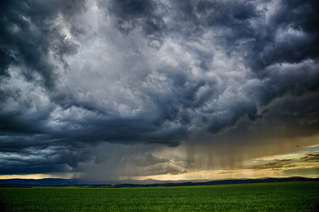 dramatic scene - meadow with clouds with and rain during summer