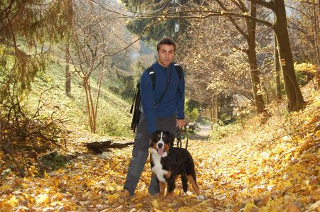Young man with his dog on autumn walk
