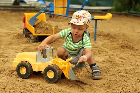 Little boy playing with children excavator in the sandbox. Archivio Fotografico
