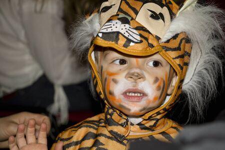 tigre bebe: Muchacho joven en un traje de tigre.