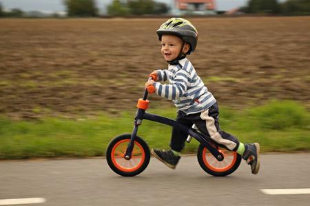 učit se: Malý chlapec na kole. Chycený v pohybu, na příjezdové cestě. Reklamní fotografie