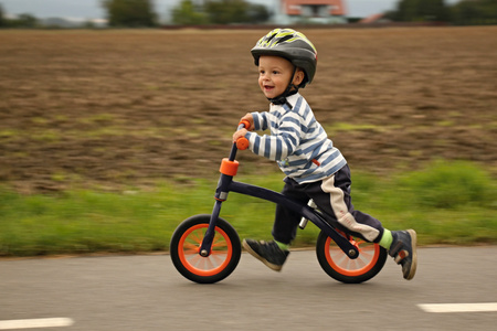 concepto equilibrio: Ni�o peque�o en una bicicleta. Atrapados en movimiento, en un camino de entrada.